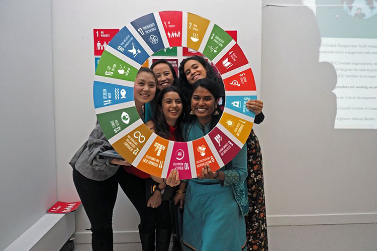 A group of five smiling young women present at a gala hold a cardboard wheel representing the UN's 2020 Agenda's logo.