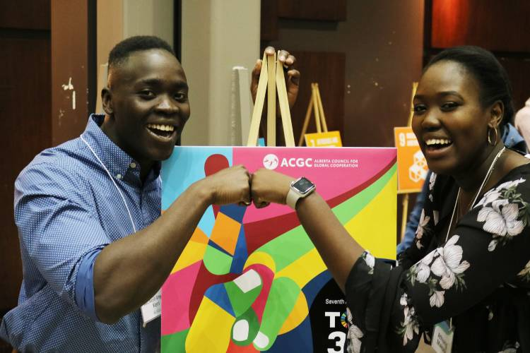 A smiling young man and woman greet each other in a cheerful manner in front of a colourful poster.