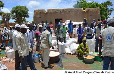 Men, women and children wait near poaches and buckets of food. © ©World Food Program/Daouda Guirou