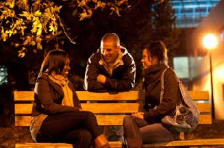 Students on bench on campus at night.