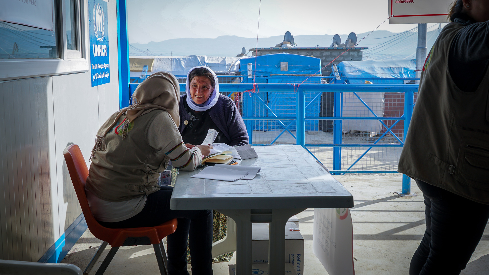 A representative from the UNHCR meets with a woman at a camp for internally displaced persons in Iraq.