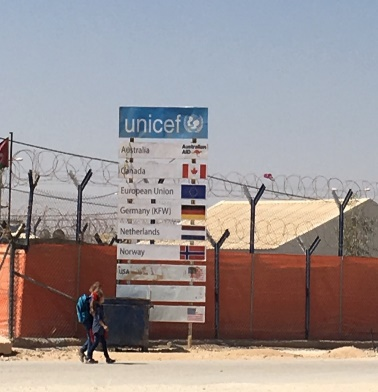 Picture of two people walking on the side of a road, in front of a tall UNICEF placard with various countries names and flags.