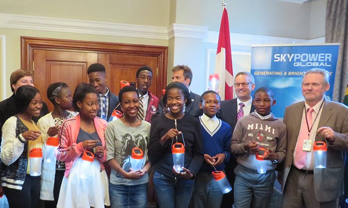 Minister Fast and Robert Davies, South Africa's Minister of Trade and Industry, with SkyPower officials and South African children holding new solar lights.