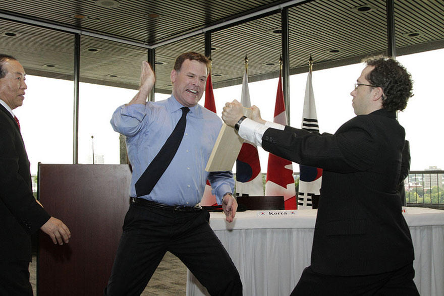 Foreign Affairs Minister John Baird breaks a piece of wood with his hand to earn an honorary black belt.