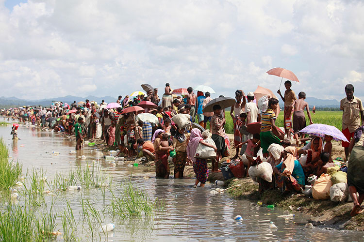 Rohingya refugees on the shore of a river in Bangledesh.