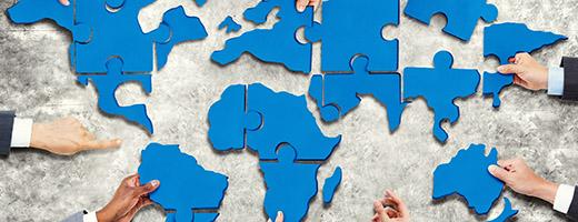 Un groupe de gens d'affaires avec puzzle formant dans la carte du monde