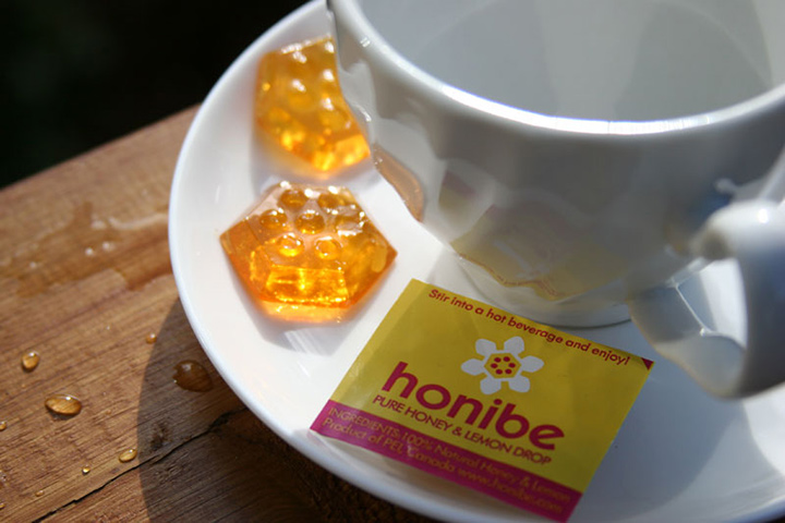 Honey and lemon product accompanying a cup of tea