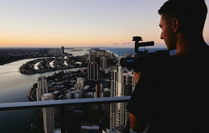 A young man holding a video camera and looking at the city shore