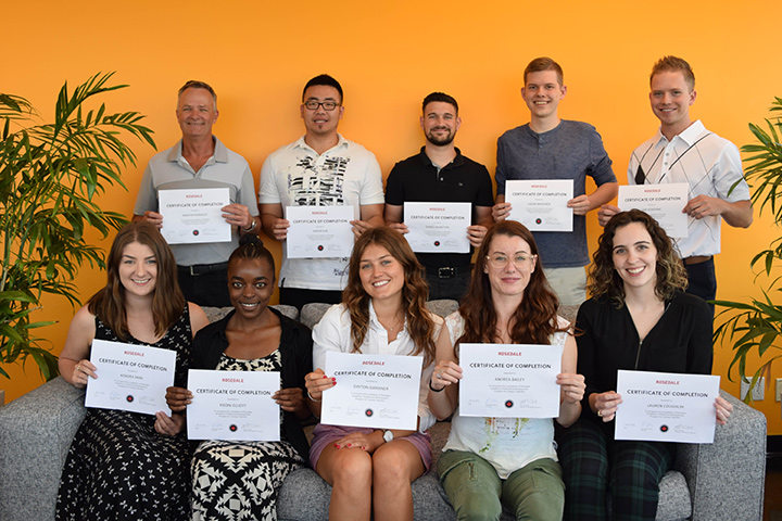 10 students holding their certificates of completion