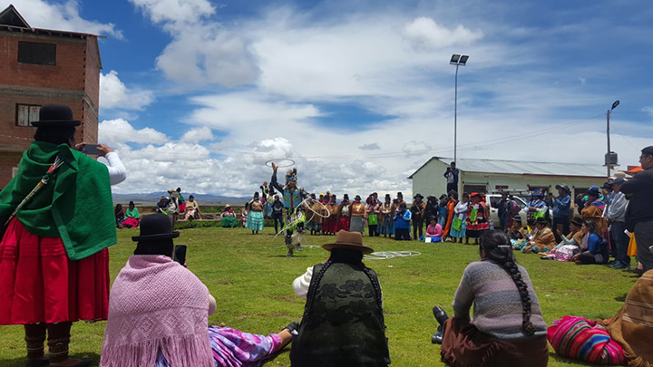 "Community members watch Alex Wells perform his traditional ""Creation"" hoop dance"