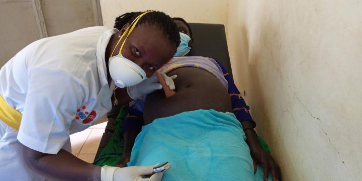 Une sage-femme masquée posant une corne de Pinard sur l'abdomen d'une femme enceinte, elle aussi masquée.