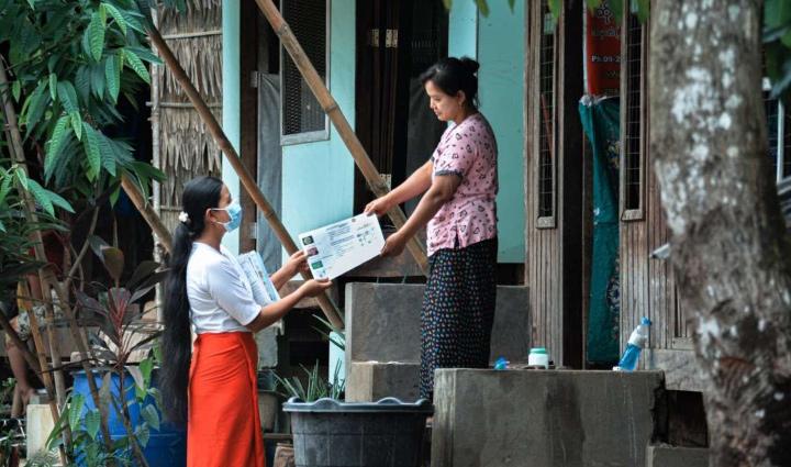 Une sage-femme masquée remet un feuillet d'information à une femme sur le pas de sa porte.