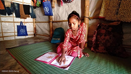 A girl sits on the floor in a shelter and reads a textbook. Around her are bags, 1 with the word <q>