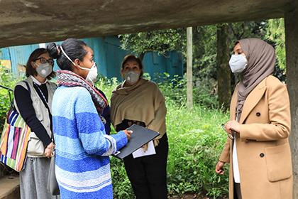Four women wearing protective masks meet outside to discuss the needs of women and children in Ethiopia.