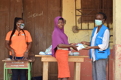 A woman wearing a mask and a UNICEF jacket hands a dignity kit to a young woman.