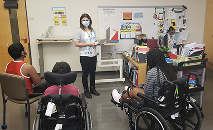 A teacher wearing a mask stands at the front of a classroom before three students. Two of them are sitting in wheelchairs and one is sitting on a chair.