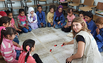 A woman sits in front of a large circle of children on the floor of a classroom.