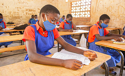 A girl wearing a mask sits at a plain wooden desk reading a book in a classroom.