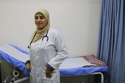 A woman wearing a medical lab coat stands in front of an examination table.