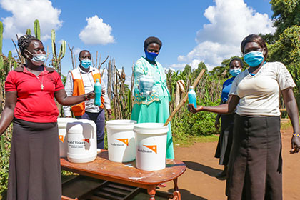 Four women and a man wearing masks show the liquid soap they made and put into bottles and large pails.