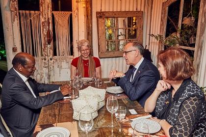 Isabelle Bérard, souriante, est assise autour d'une table avec deux hommes et une femme.