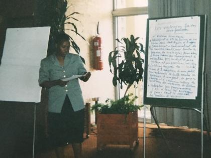 Isabelle BérarUne femme du Rwanda, papiers en main, devant un bloc de papier sur lequel sont écrites plusieurs phrases.