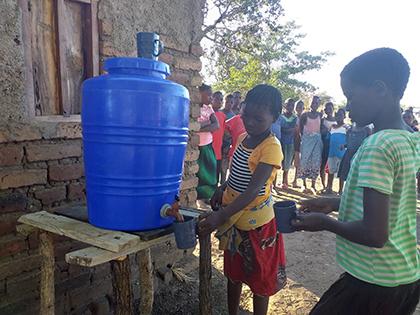 Une fillette remplit une tasse d'eau à l'aide d'un distributeur. Plusieurs enfants la regardent faire.